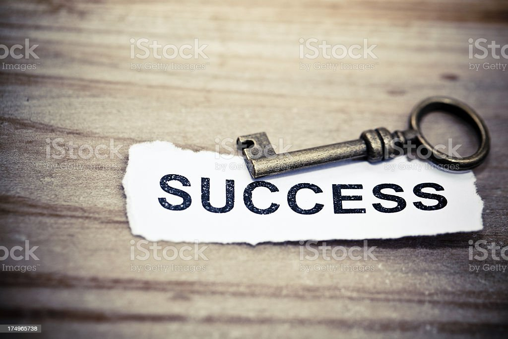 A old key next to success in text stock photo
