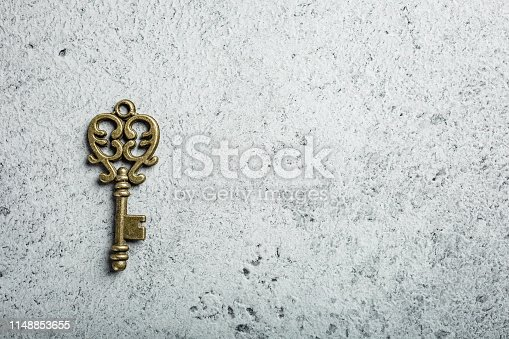 Old key on old gray concrete background. Copy space, top view.