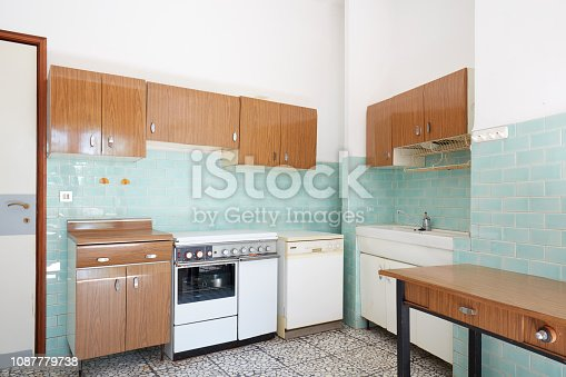 Old kitchen interior with turquoise tiles in old house in Italy