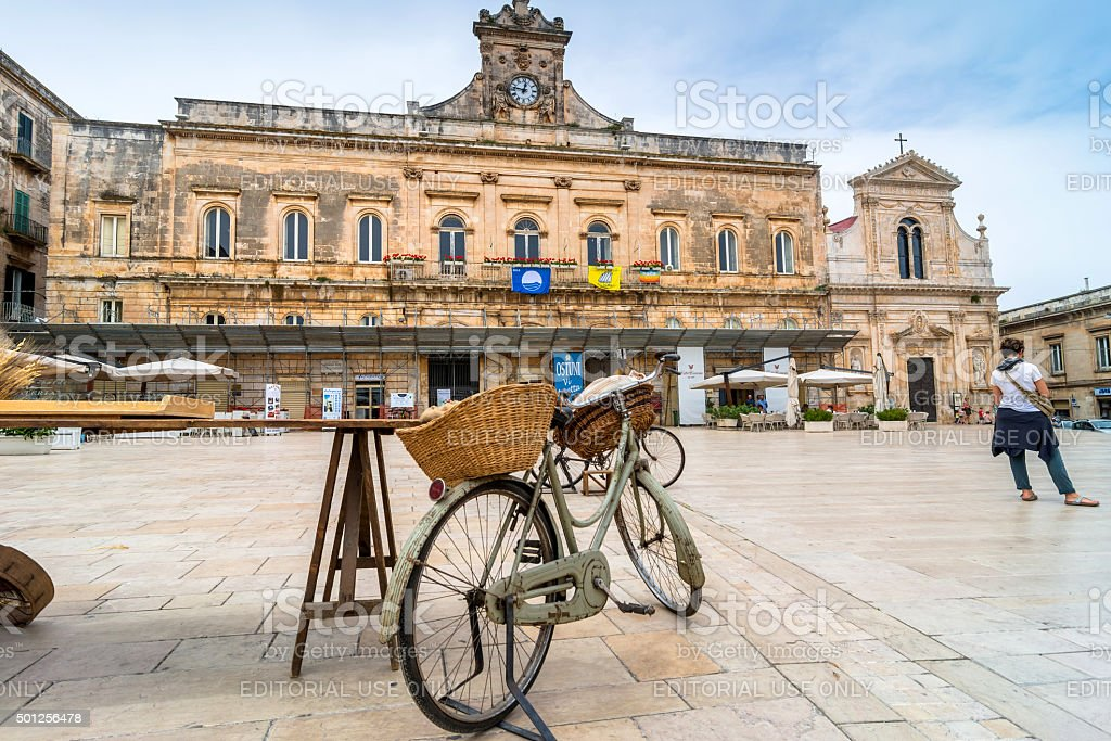 old knife grinder bicycle and main square in Ostuni, Italy stock photo