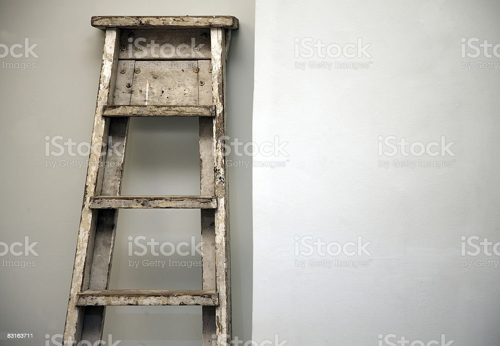 Old ladder resting against a clean wall royalty-free stock photo