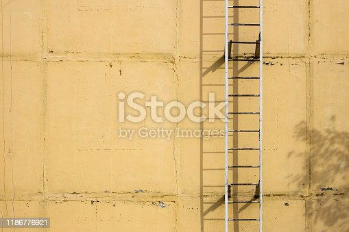 639291528istockphoto Old ladders on blank yellow wall 1186776921