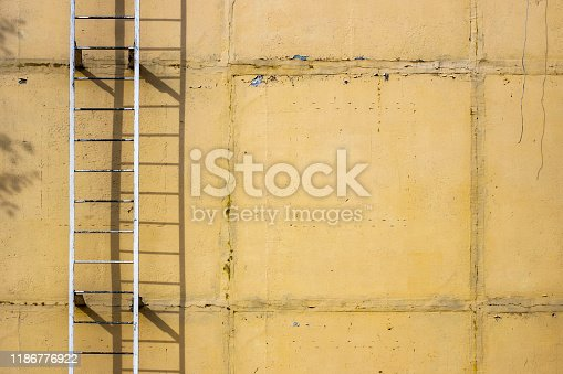 639291528istockphoto Old ladders on blank yellow wall 1186776922