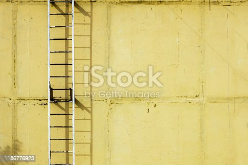 639291528istockphoto Old ladders on blank yellow wall 1186776923