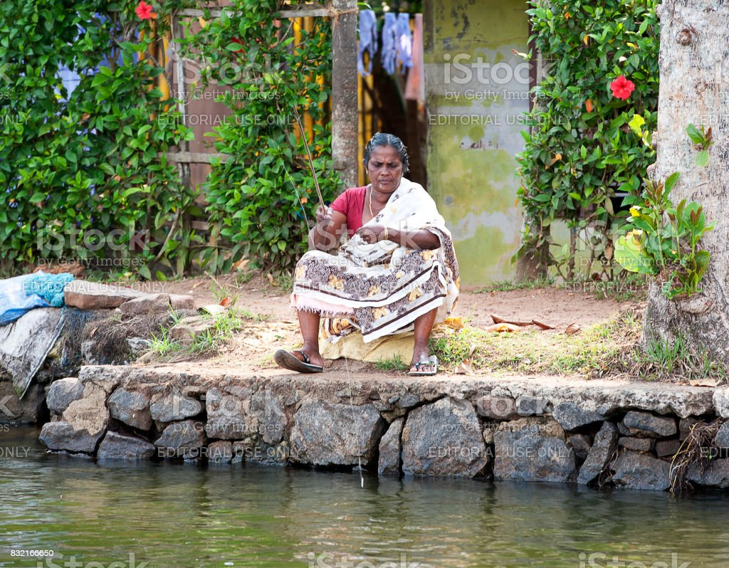 Old lady fishing, Keralan backwater lagoon, Kumarakom, Kerala, Southern India. stock photo