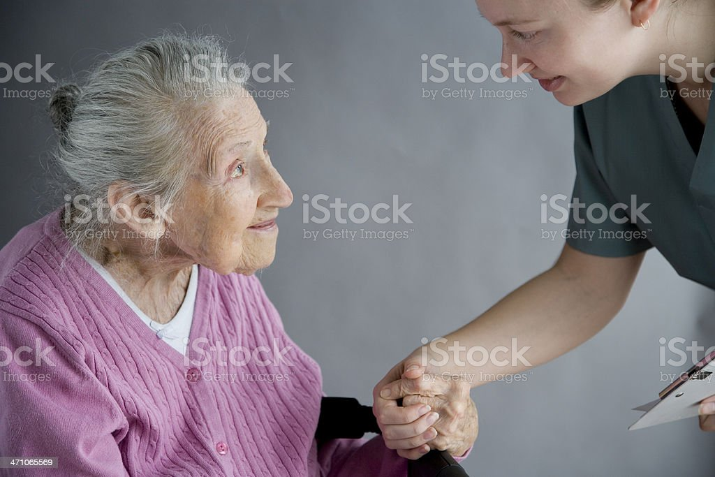 Old lady holding the hand of her nurse royalty-free stock photo