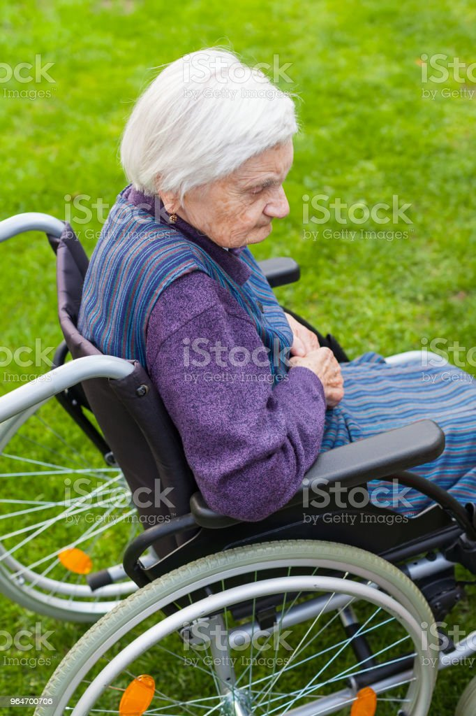 Old lady sitting in wheelchair royalty-free stock photo