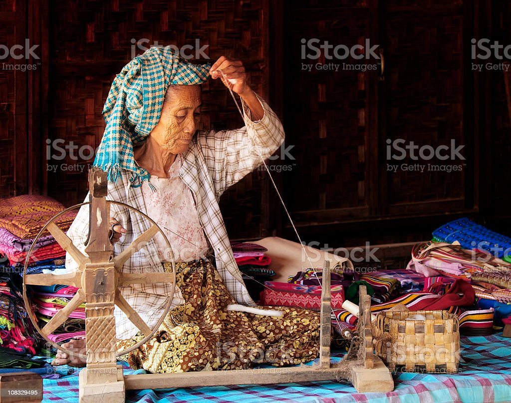 Old Lady Spinning Cotton stock photo