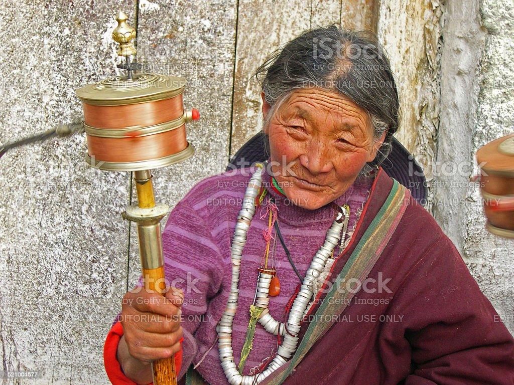 Old lady turning prayer wheel stock photo