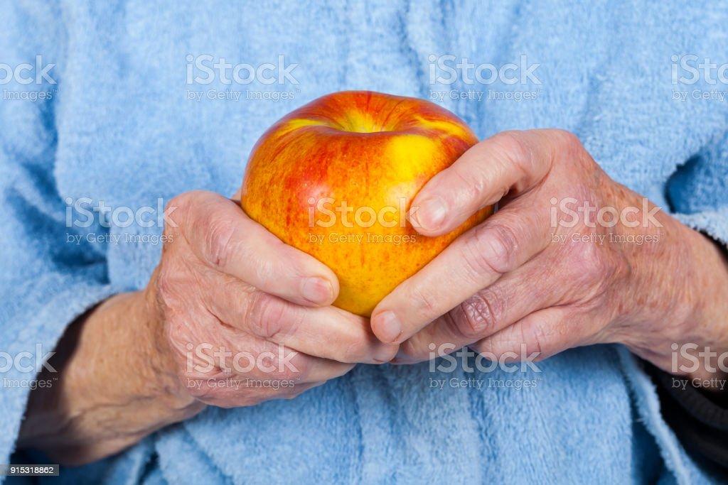 Alte Dame Hände halten einen Apfel – Foto