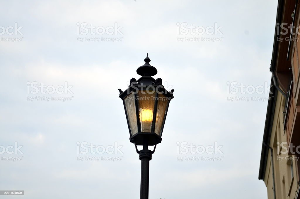 old lantern at a street in berlin lightning stock photo