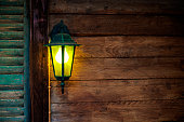 Yellow light bulb glowing in an  old lantern on wooden wall