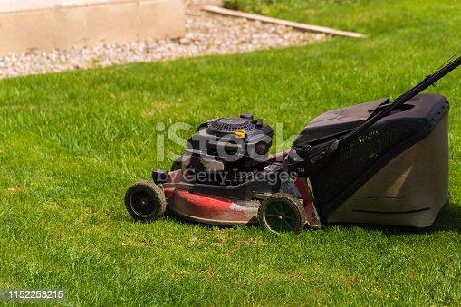 istock Old Lawn mower cutting green grass in backyard.Gardening background. 1152253215