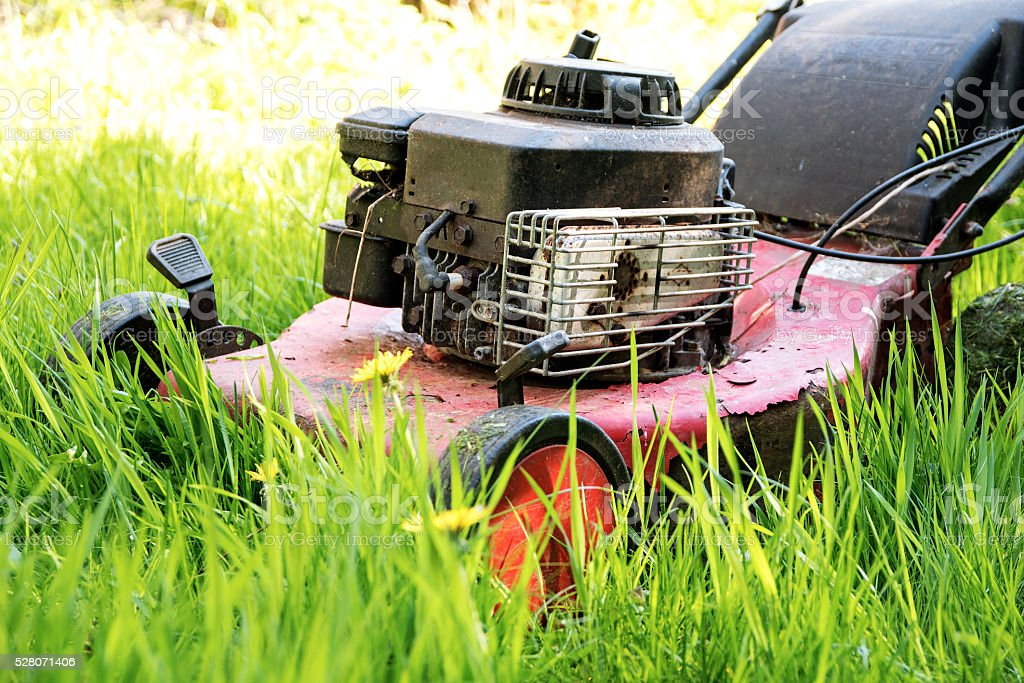 old lawn mower in tall grass, neglected gardening stock photo