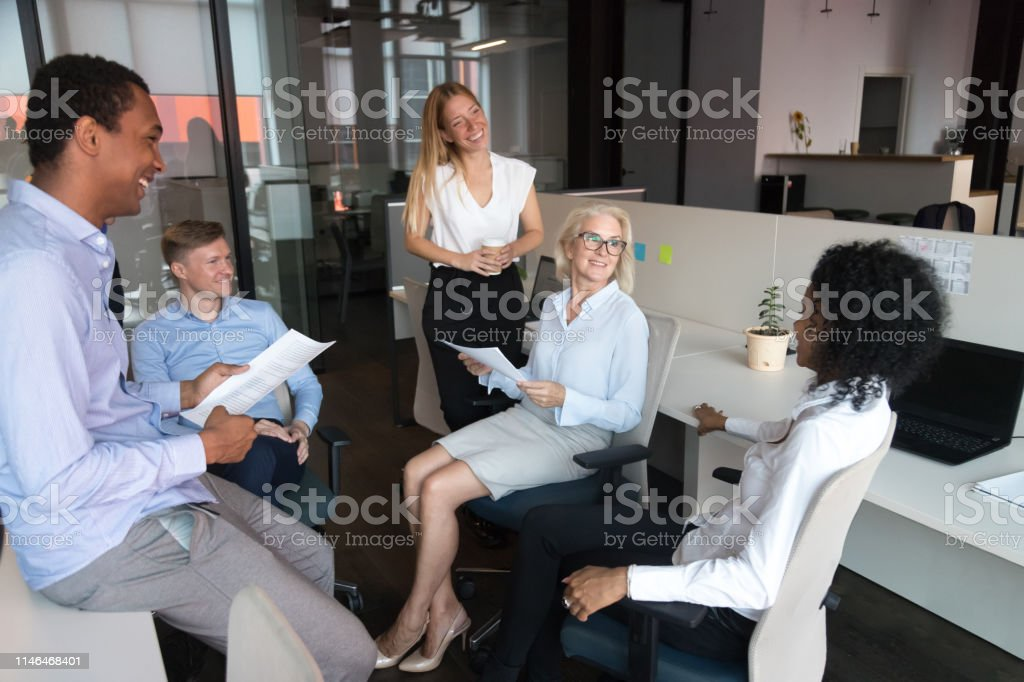 Old female leader coach talking to happy sales team employees...
