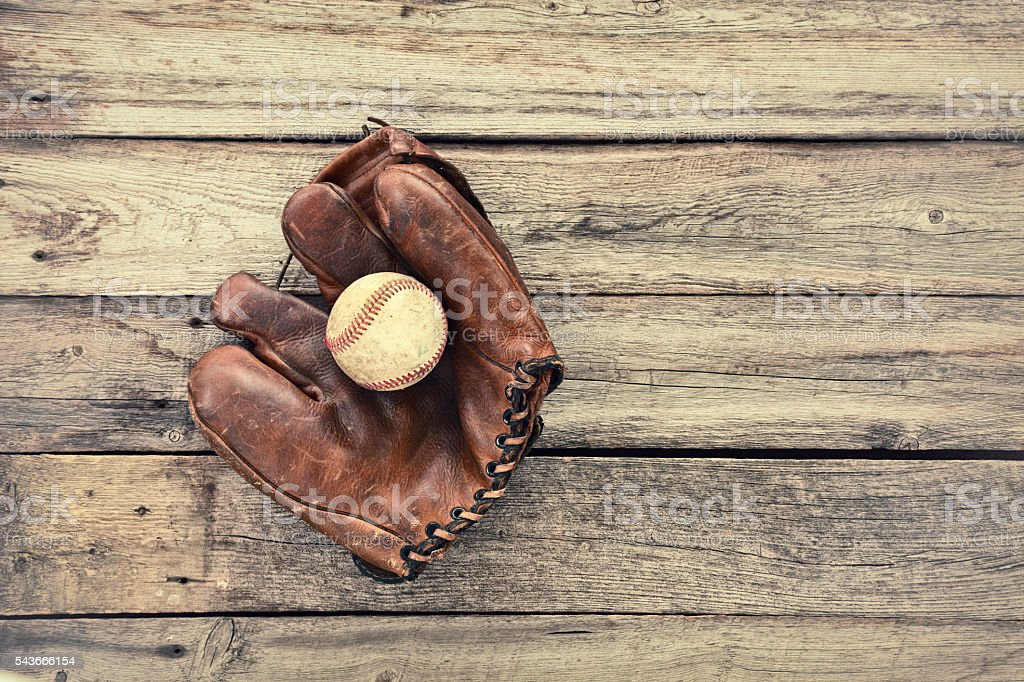 Old leather baseball mitt and ball on grunge wood background royalty-free stock photo