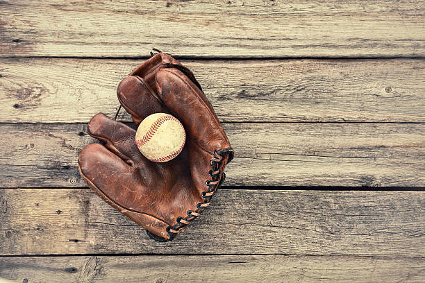 Old leather baseball mitt and ball on grunge wood background stock photo