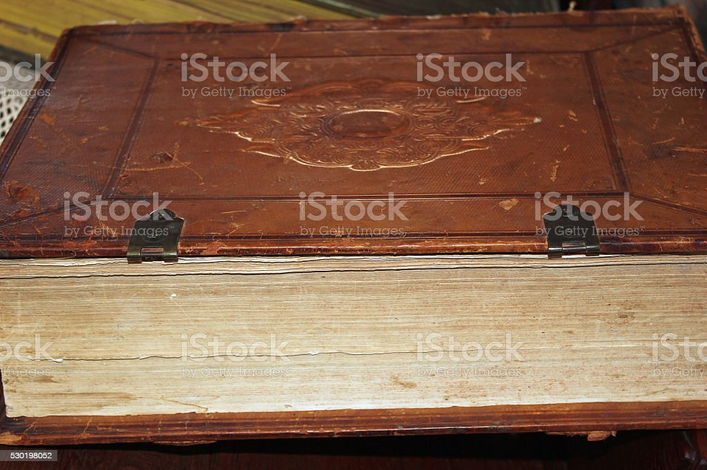Old leather bound book lying on its side stock photo