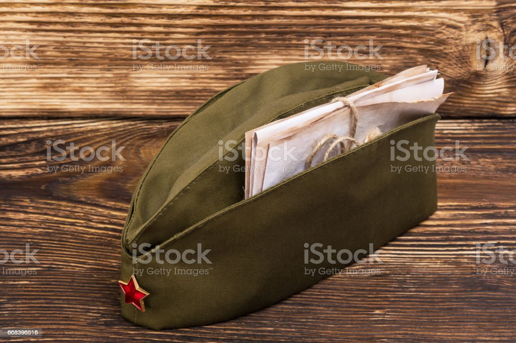 Old letters lie in a military cap with a red star, on an old table stock photo