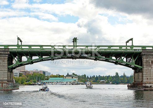 Moody blue sky cloudscape over the old lifting bridge, an iconic sight with its iron and steel girder spans between stone pillars in Seattle, seen over the calm surface of Lake Union as motorboats pass beneath on this central lake in the city, Washington State, USA