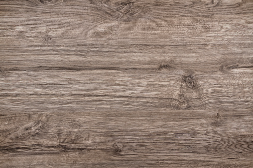 Directly above view of a light brown wood background.  This background features a distinguished wood grain pattern complete with light swirls, wavy lines and occasional knots. The color of the wood appears darker near the top and bottom, but becomes lighter near the middle. A small knot is visible near the center. Another small knot is visible in the middle of the bottom.