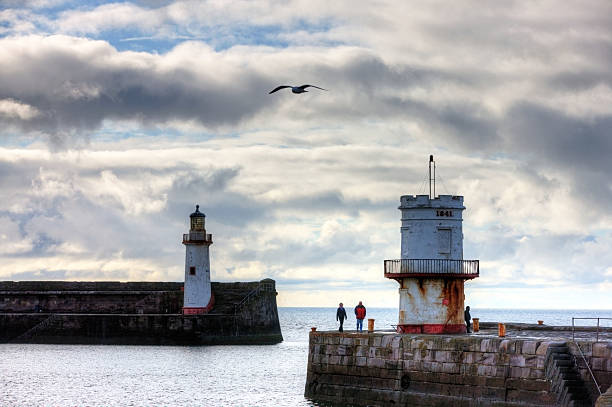 Old lighthouse on Cumbria coastal town Whitehaven, England - March 17, 2013: Old lighthouse on Cumbria coastal town of Whitehaven. A couple are pictured walking around the circular building while a man fishing leans up against it northwest england stock pictures, royalty-free photos & images
