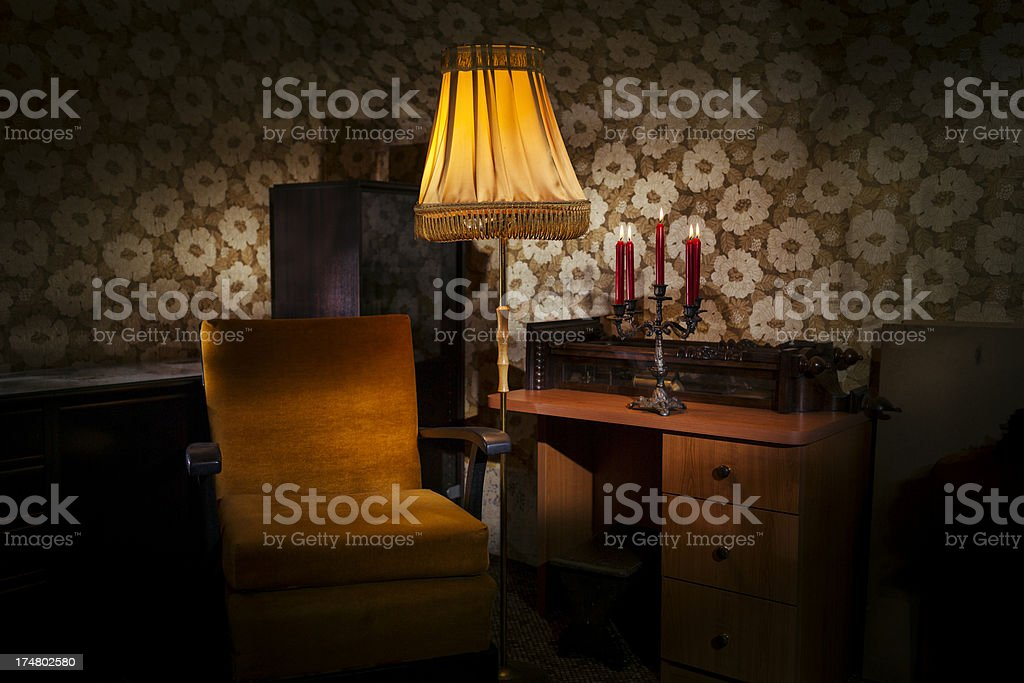 Old living room with chair and floor lamp.