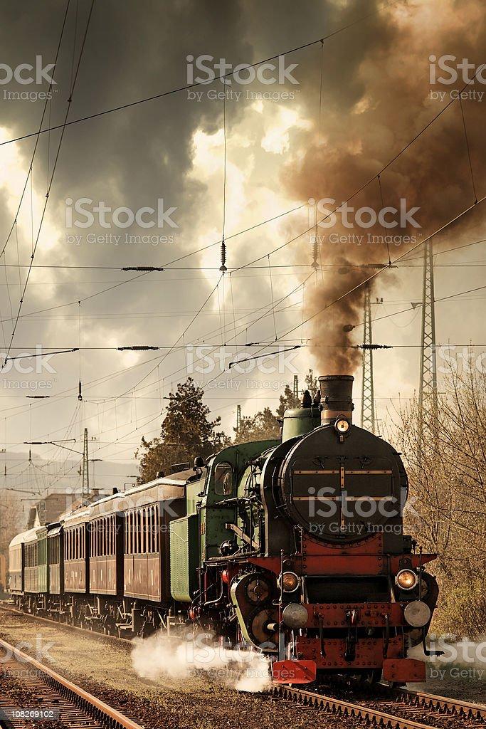 old locomotive leaving the railway station stock photo