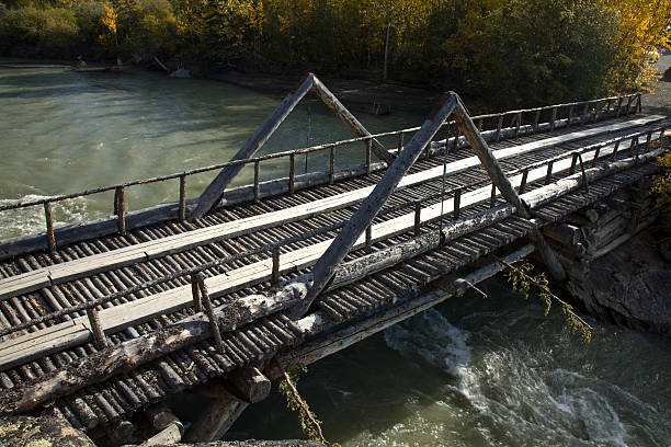 old log bridge over river near haines junction, yukon - yt stock pictures, royalty-free photos & images