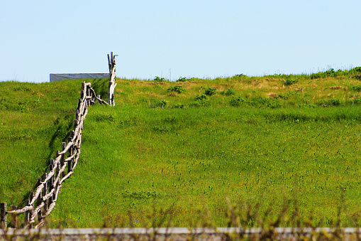 An old fashioned log fence on a hill