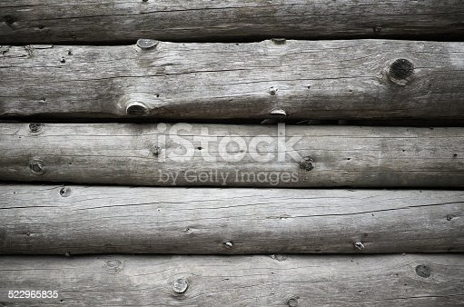 Old wooden house wall, gray logs with knots