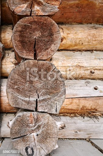 Old wooden house wall, brown logs with knots, cut texture rings