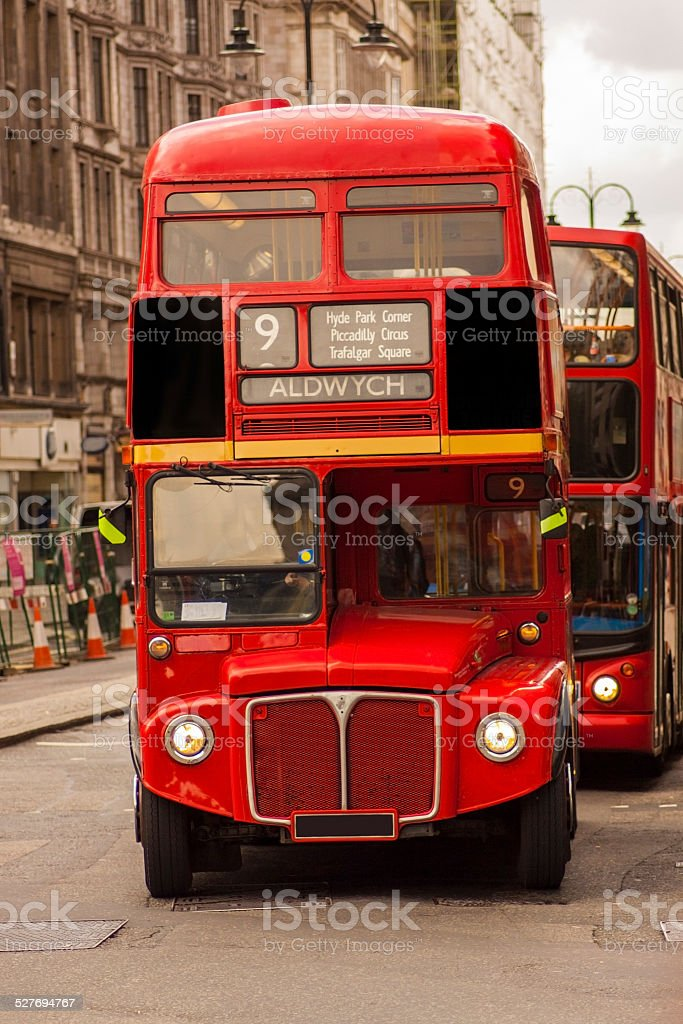 Old London bus being followed by a newer model stock photo