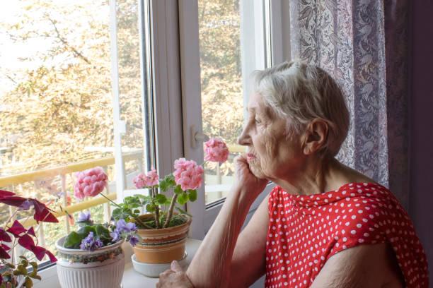 Alte einsame Frau sitzt in der Nähe des Fensters in seinem Haus. – Foto