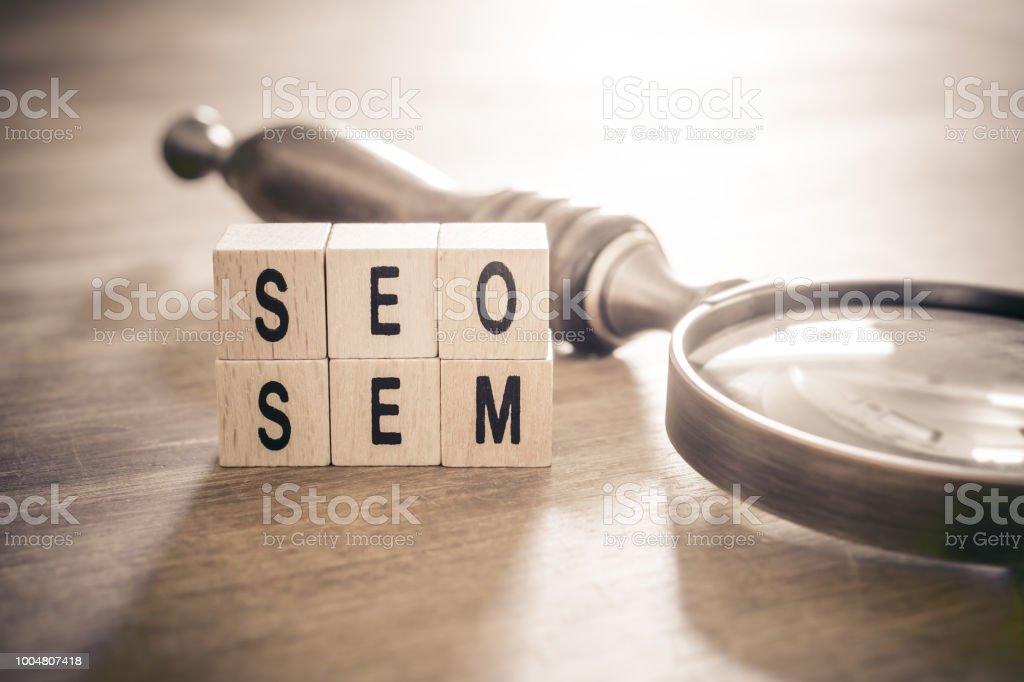Antigua lupa vidrio mintiendo al lado de SEO y SEM bloques en colores monocromáticos - posicionamiento en buscadores y Marketing concepto - foto de stock