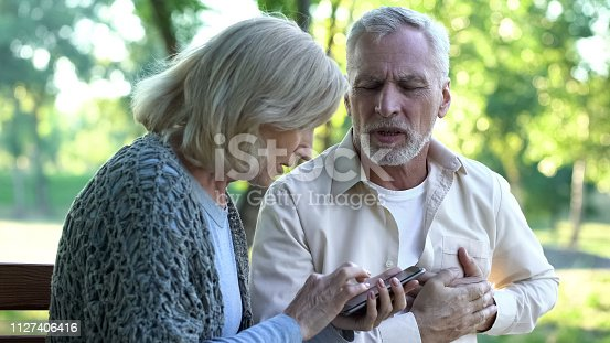 istock Old male having chest pain, heart attack, worried wife calling 911, emergency 1127406416