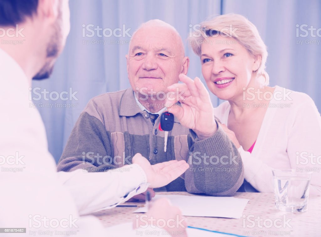 Old man and mature woman signing contract car lease stock photo