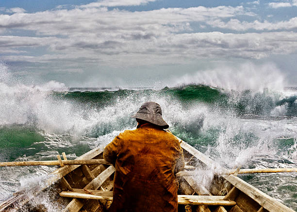 Old man and the Sea in a Skiff Old man and the sea, in a rowboat or skiff paddling and fighting the waves of the ocean. fisherman stock pictures, royalty-free photos & images