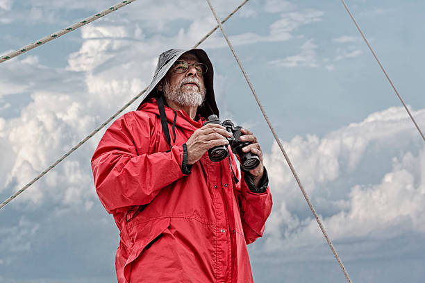 Old Man and the Sea Looking Out A man on the bow of a sailboat overlooks checking the seas and the weather. sailor stock pictures, royalty-free photos & images