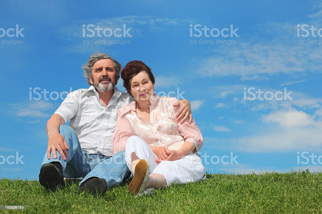 Old man and woman sitting on green lawn stock photo