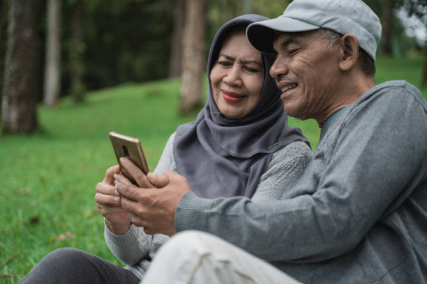 old man and woman using mobile phone in the park stock photo