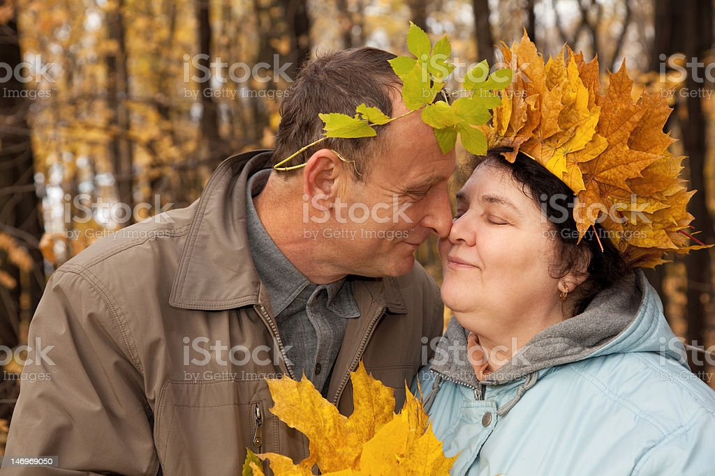 Old man and woman with wreath of maple leaves stock photo