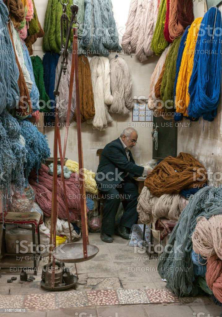 old iranian shop keeper in his shop at a market