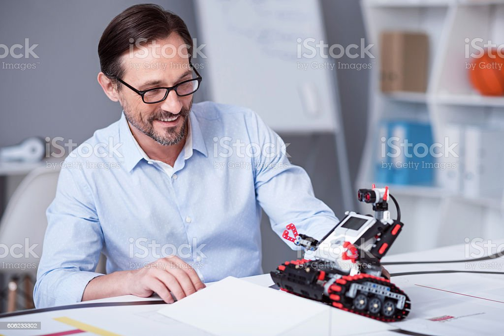 Old man being exited to test a little robot stock photo