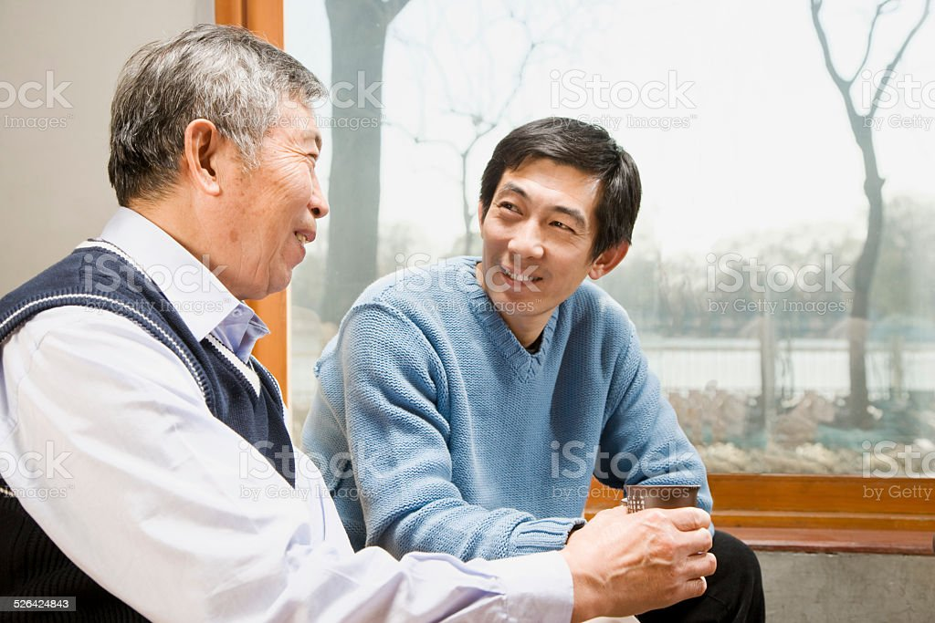 Old Man Chatting with His Son stock photo