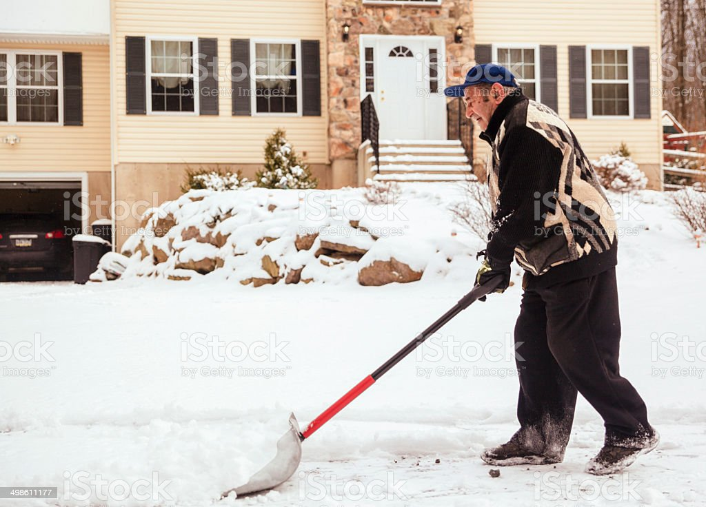 Old man cleaning doorway before house from snow after snowfall stock photo