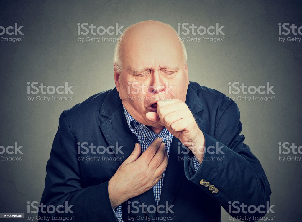 Old man coughing holding fist to mouth isolated on gray background stock photo
