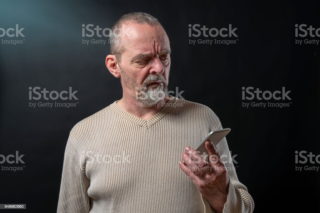 old man does not understand his smart phone stock photo