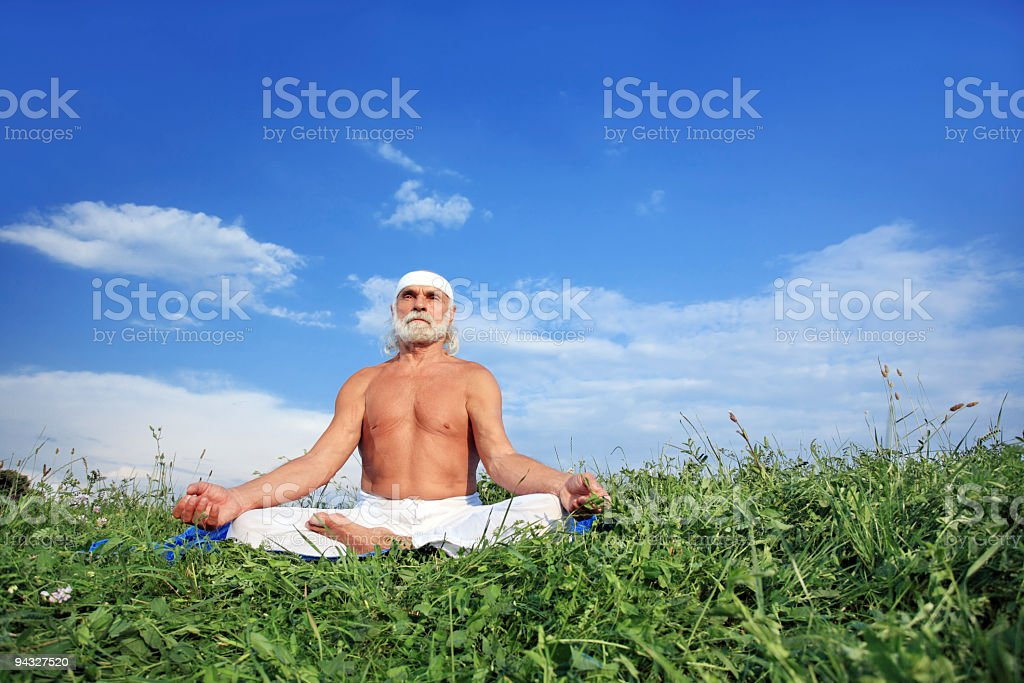 Old man doing meditation on meadow. royalty-free stock photo