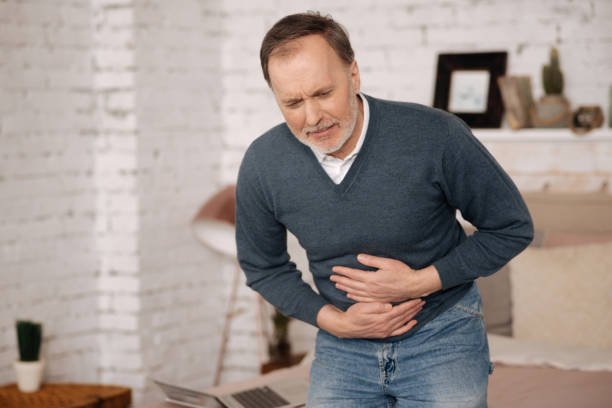 Old man feeling big discomfort in stomach stock photo